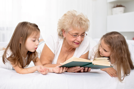 Grandmother is reading a book to her granddaughters