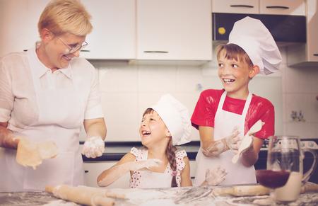 Grandmother with grandchildren baking cookies prepare dough