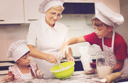 grandmother and grandson: Grandmother with grandchildren baking cookies prepare dough