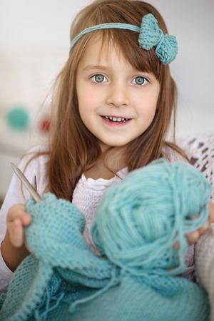 needle and thread: Closeup of cute little girl knitting with knitting-needle at home Stock Photo