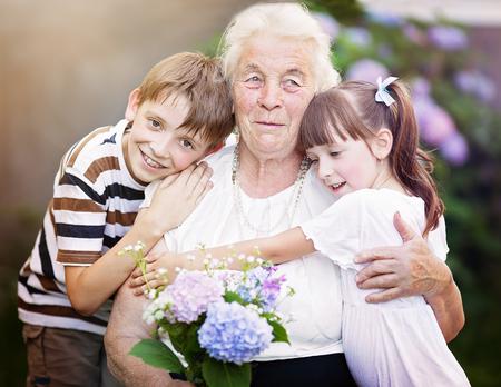 the great grandmother: Closeup summer portrait of happy grandmother with grandchildren outdoors