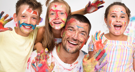 Portrait of a cute happy father with children painting and having fun. They are showing their hands painted in bright colors   Фото со стока