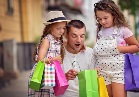Happy father with children have a successful day of shopping