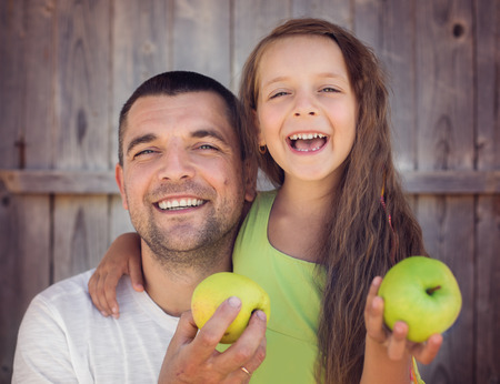 Happy father with daughter holding green apple and smiling outdoors Фото со стока