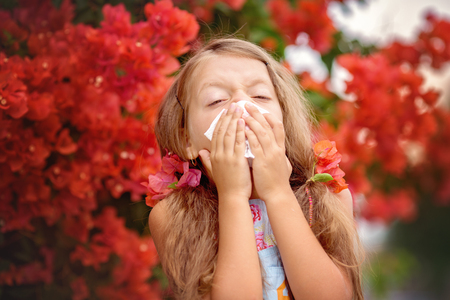 Allergy. Little girl is blowing her nose near spring tree in bloom Stock Photo