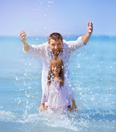 Happy father and daughter playing together, running and jumping on a beach on a sunny hot summer day