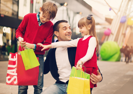 Happy father with children have a successful day of shopping    Stock Photo