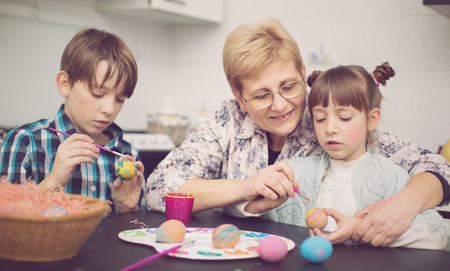 Grandmother with grandchildren are coloring eggs for Easter,