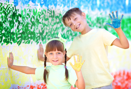 Playing with colors. Beautiful children with colorful hands, creative child concept Stock Photo