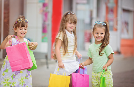 three smiling little girls with shopping bags walking in the city