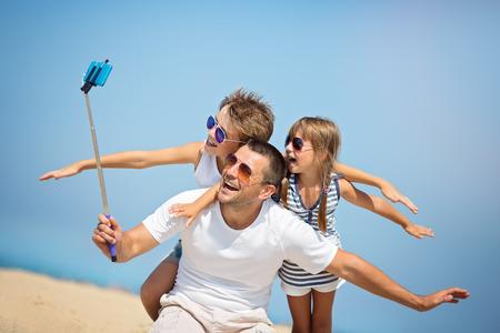 Padre con los niños que toman autofoto en la playa en el tiempo del día. Foto de archivo - 73381580