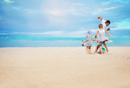 Father with children playing football on the beach at the day time. Stock Photo