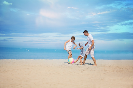 Father with children playing football on the beach at the day time. Standard-Bild