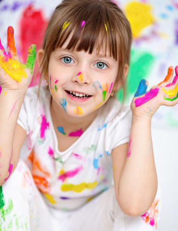 little girl showing her hands painted in bright colors