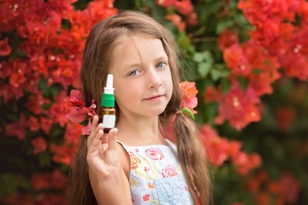 Allergy. Little girl  near spring tree in bloom with nasal spray Stock Photo