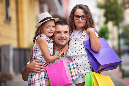 Happy daughters hugging father with shopping bags photo
