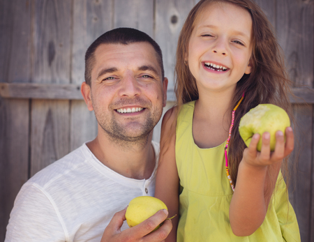 Father with daughter eating apples together photo