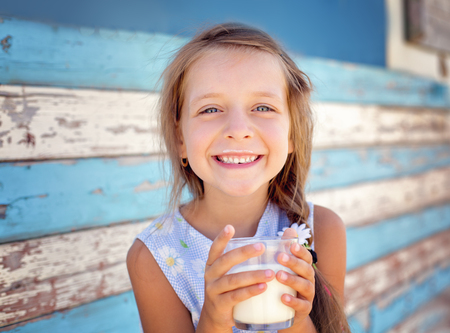 Cute little girl is drinking milk outdoors photo
