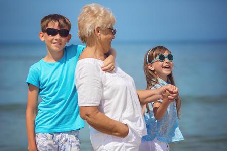 Summer portrait of grandmother with her grandchildren having fun