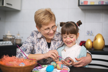 Grandmother with granddaughter are coloring eggs for Easter