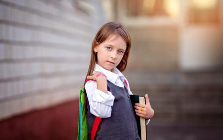 niños saliendo de la escuela: Feliz colegiala va a la escuela con los libros