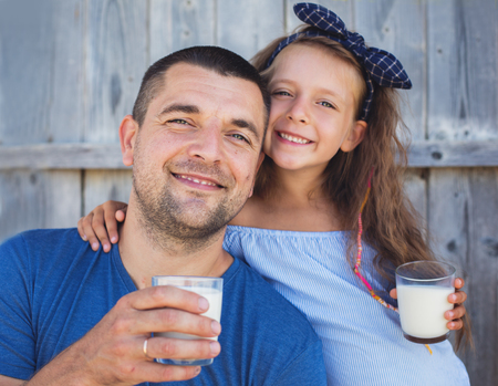 Father with daughter is drinking milk and having fun
