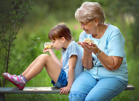 grandaughter: Grandmother with grandaughter are playing with chickens outdoors Stock Photo
