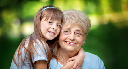 Closeup summer portrait of happy grandmother with granddaughter outdoors