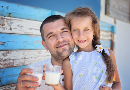 Cute little girl with her father holding glasses of milk over a wooden background.