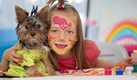 dog school: Cute little girl with her friend puppy are playing with paints and painting