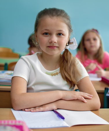 Lesson. Little schoolgirl is listening her teacher in class