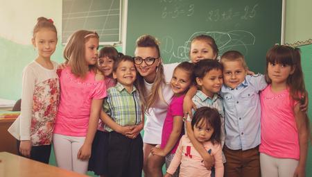 Lesson. Little schoolchildren are listening their teacher in class Фото со стока