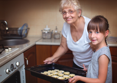 Cooking is fun. Happy grandmother  with cute  granddaughter cooking cakes in the kitchen Фото со стока
