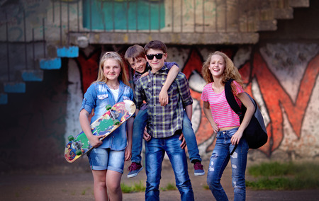 Portrait of happy teens having fun by painted wall Фото со стока