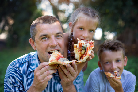 Picnic.Father with children eating pizza. Фото со стока
