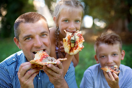 Picnic. Cute family, father with his son and daughter are eating pizza in the park. Фото со стока