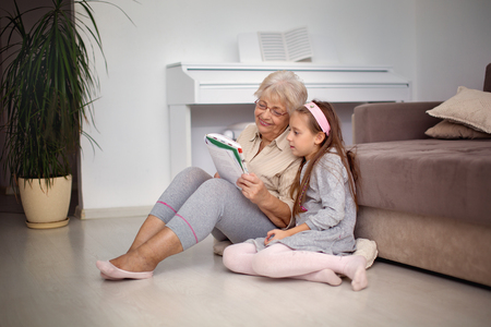 Grandmother is reading a book to her granddaughter Фото со стока