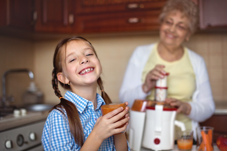 Grandmother with granddaughter are preparing fresh juice from apples ad carrots