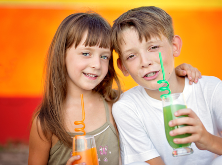Cute , happy , smiling children are drinking juice