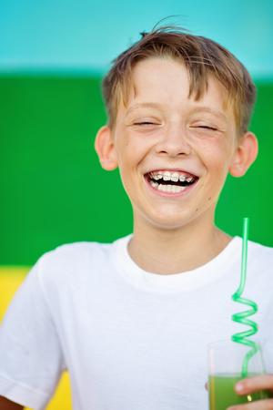 Cute , happy , smiling boy is drinking juice