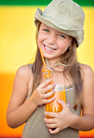 Cute, smiling little girl is drinking juice