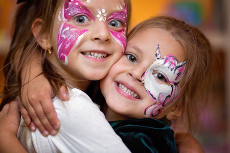 Funny cute little girls with painting faces are hugging ang having fun Фото со стока