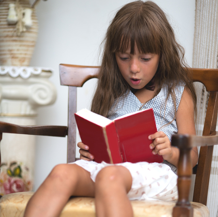 Cute little girl is reading book
