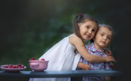 Cute little kids eating cherries in summer garden
