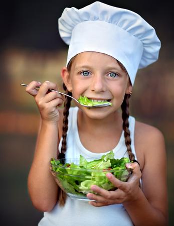 Closeup portrait of cute little girl eating salad Фото со стока