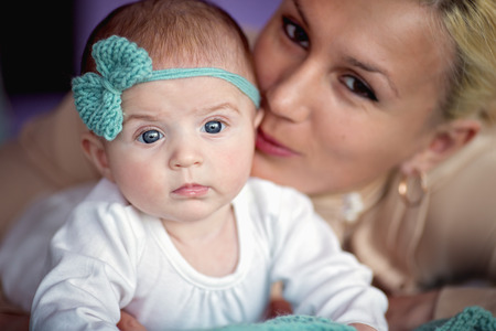 Closeup portrait of cute baby with mother