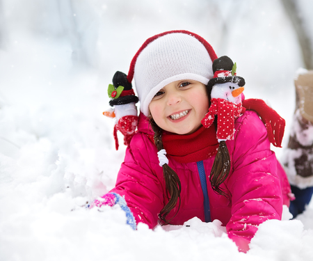 Closeup winter portrait of cute little girl playing and having fun