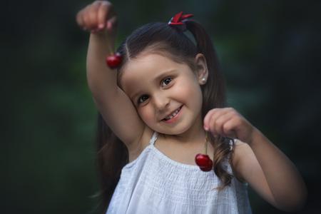 Cute little kids eating cherries in summer garden. Фото со стока