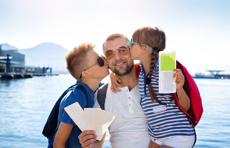 Summer holidays.Father with children are waiting summer sea vacation Фото со стока