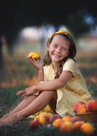 Cute little girl eating peach in the garden